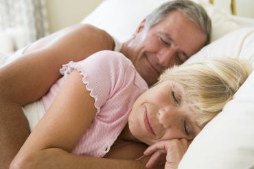 Couple lying in bed sleeping
